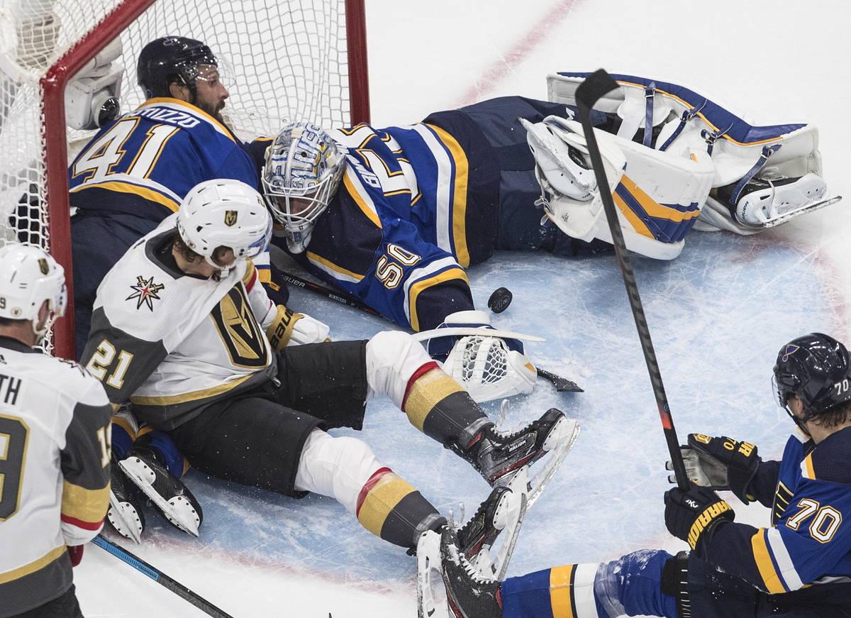 St. Louis Blues goalie Jordan Binnington (50) makes a save as players crash into the net during ...