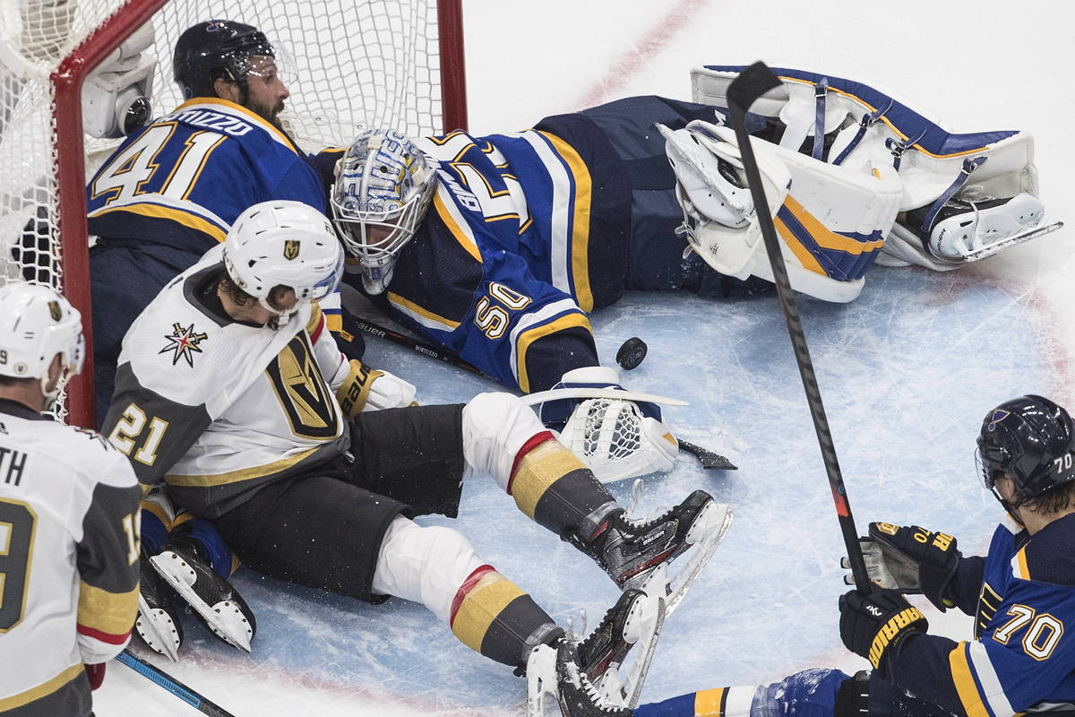 St. Louis Blues goalie Jordan Binnington (50) makes a save as players crash into the net during ...