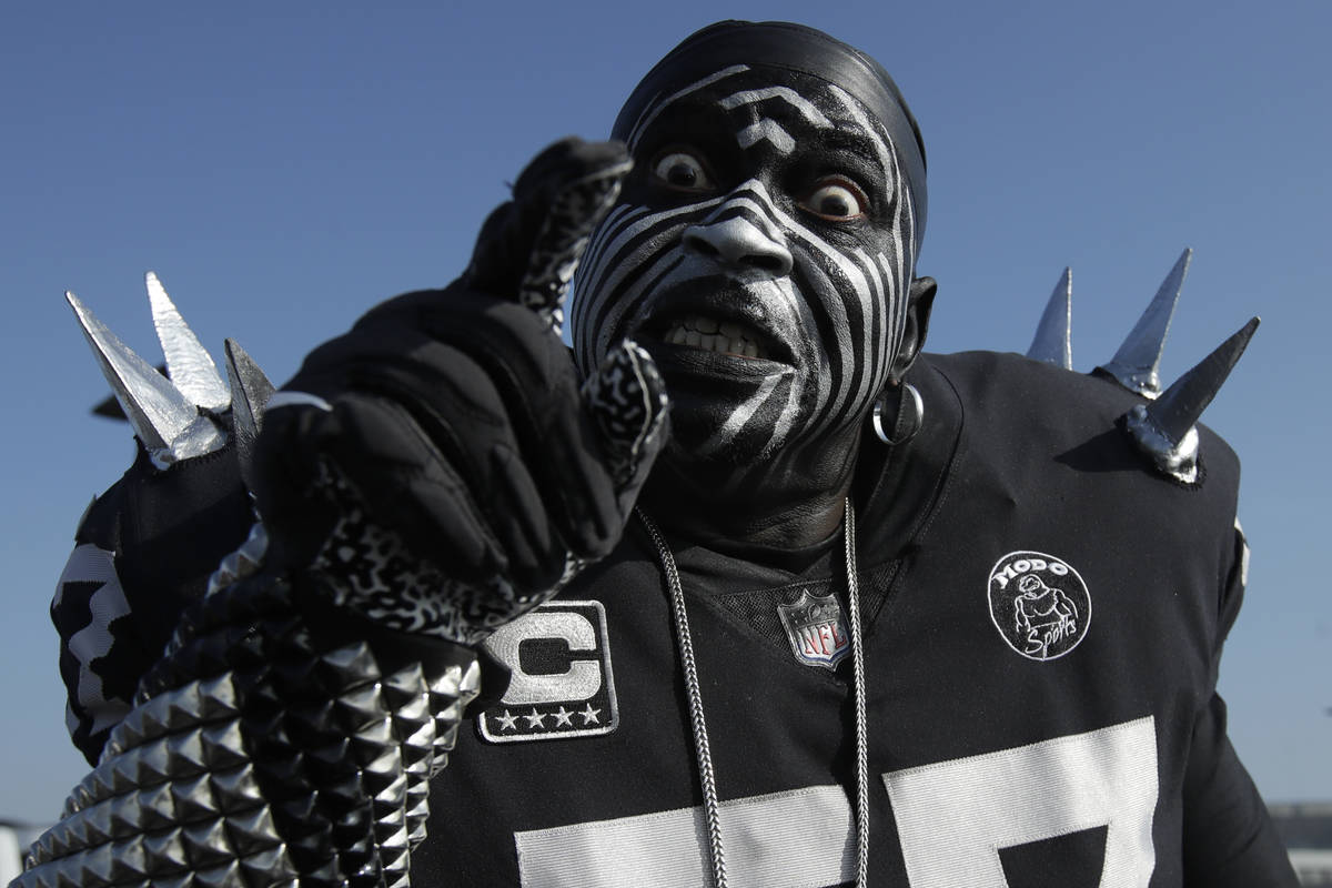 Oakland Raiders fan Violator poses for photos while tailgating at RingCentral Coliseum before a ...
