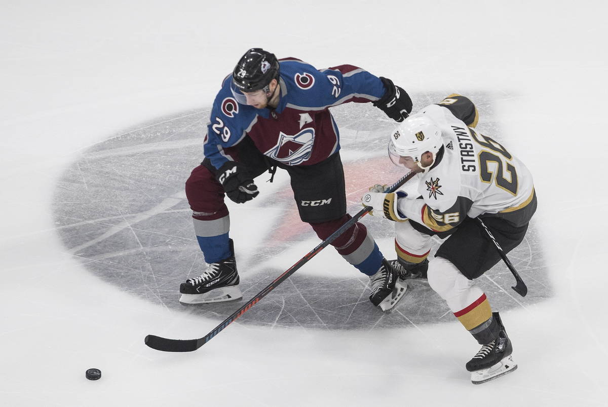 Colorado Avalanche's Nathan MacKinnon (29) and Vegas Golden Knights' Paul Stastny (26) battle f ...