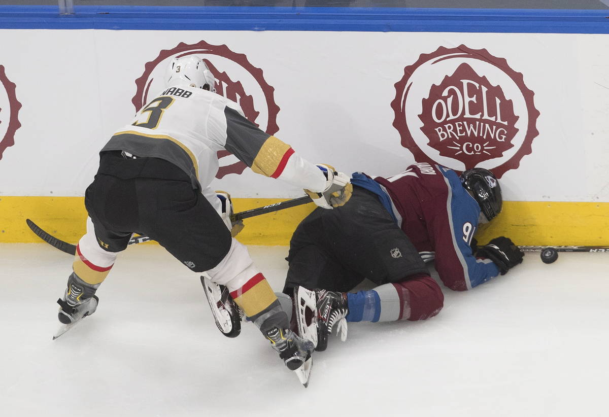 Colorado Avalanche's Nazem Kadri (91) is checked into the boards by Vegas Golden Knights' Brayd ...
