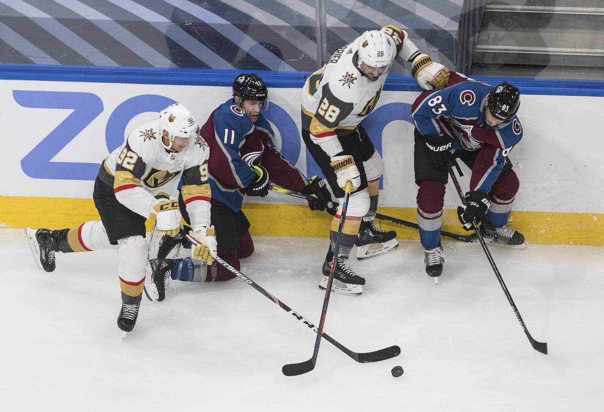Colorado Avalanche's Matt Calvert (11) Matt Nieto (83) battle for the puck with Vegas Golden Kn ...