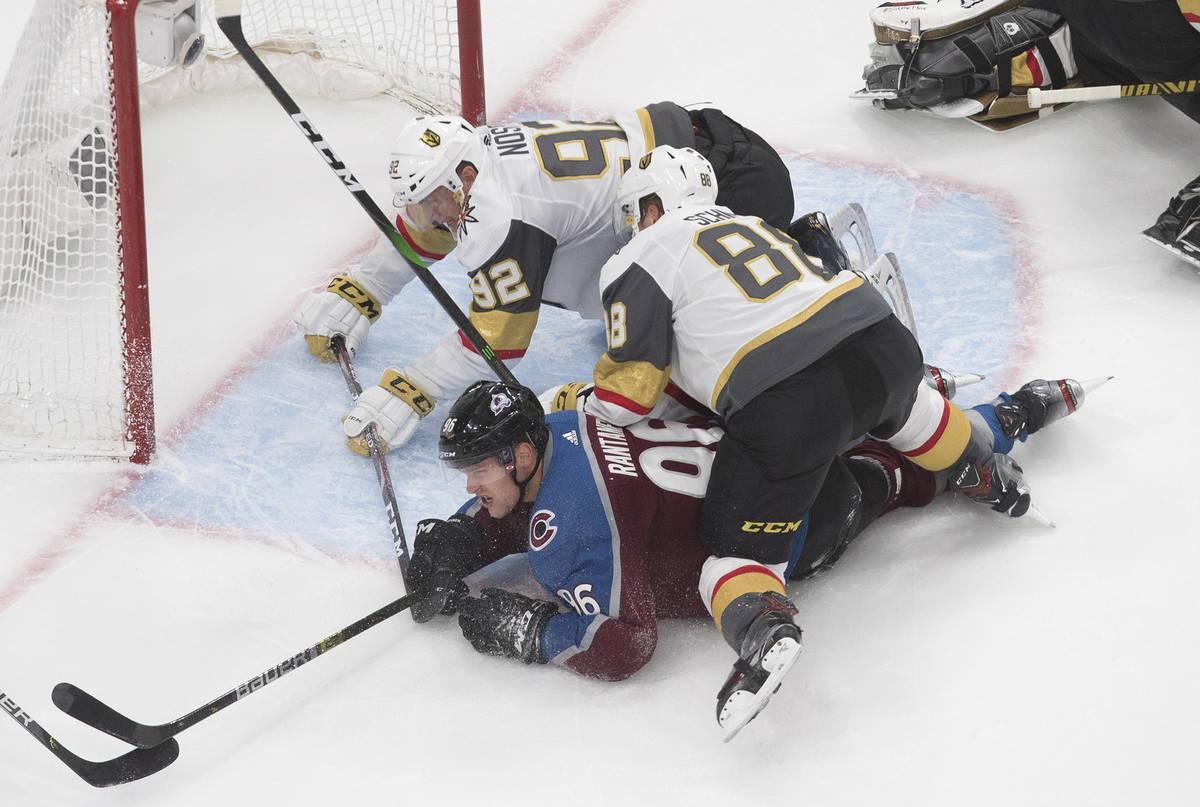Colorado Avalanche's Mikko Rantanen (96) is taken down by Vegas Golden Knights' Tomas Nosek (92 ...