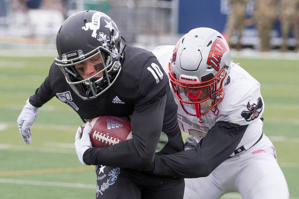 Nevada wide receiver Ben Putman (10) is grabbed by UNLV linebacker Javin White (16) in the firs ...