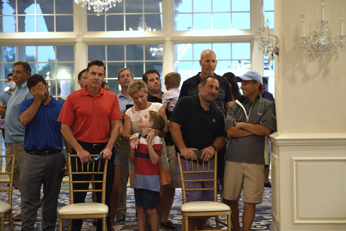People stand behind chairs as they wait to watch President Donald Trump speak at Trump National ...