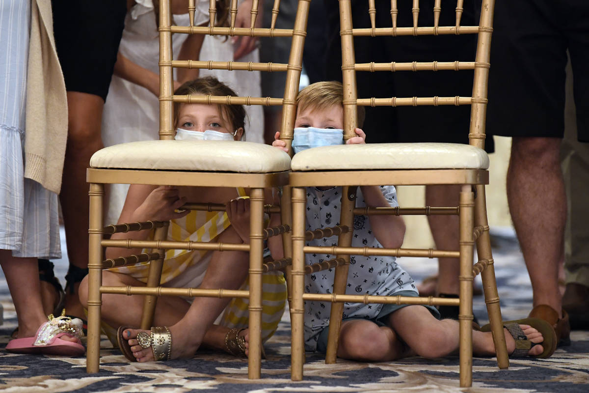 Children sit behind chairs as they wait to watch President Donald Trump speak at Trump National ...