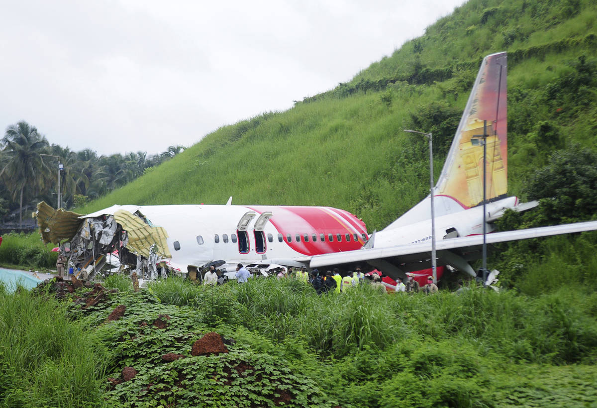 Officials stand on the debris of the Air India Express flight that skidded off a runway while l ...