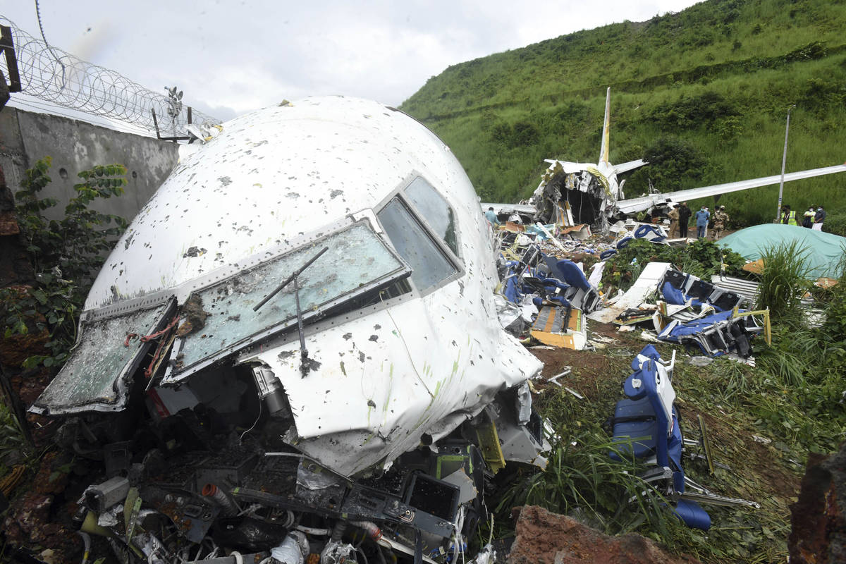 People stand by the debris of the Air India Express flight that skidded off a runway while land ...