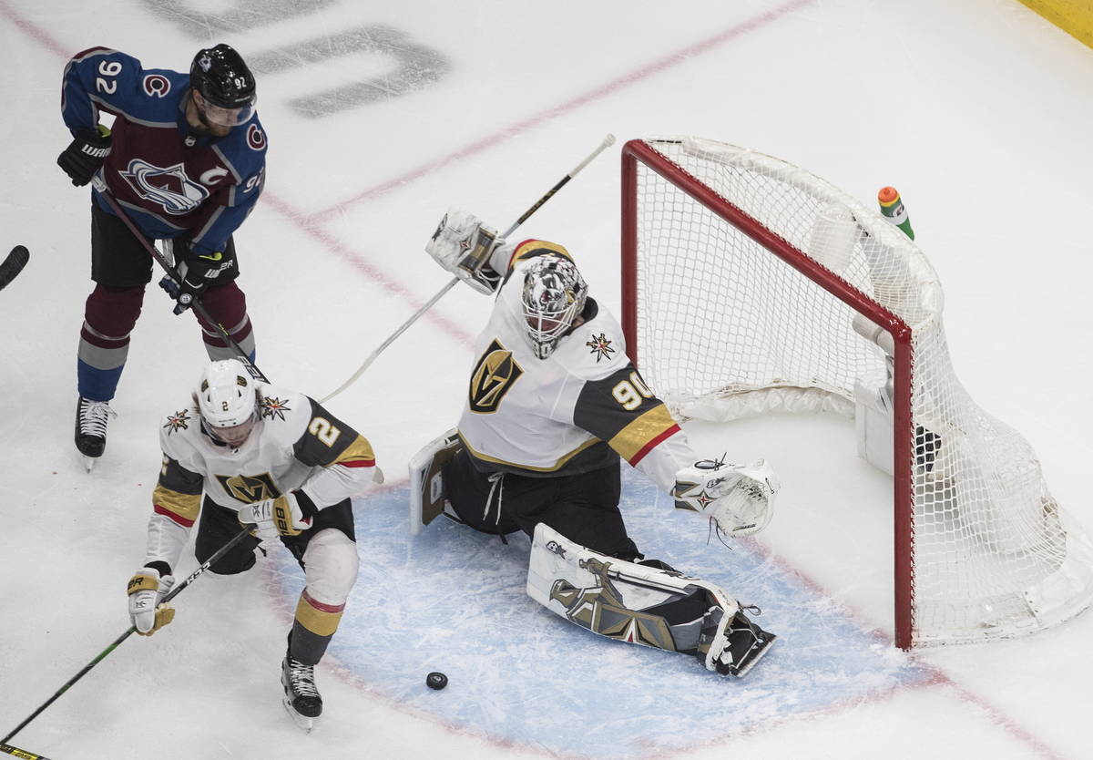 Colorado Avalanche's Gabriel Landeskog (92) and Vegas Golden Knights' Zach Whitecloud (2) look ...