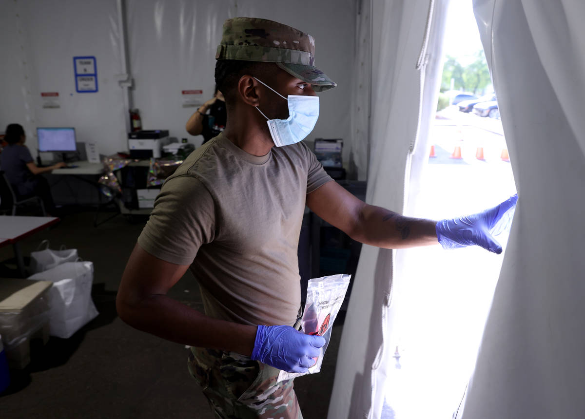 Nevada Air National Guard Airman 1st class Kevin Davis works on curbside testing for COVID-19 a ...