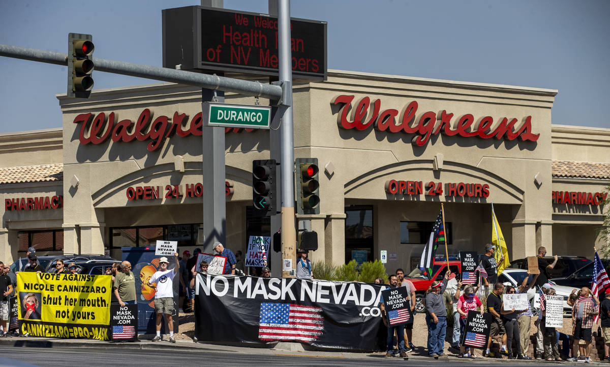 Supporters line the sidewalks during a No Mask Nevada rally to oppose the face mask mandate and ...