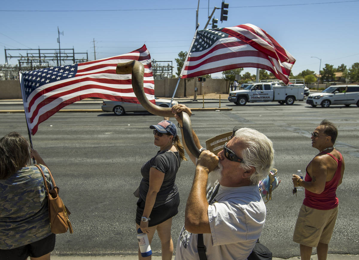 Brand Thornton, center, blows a shofar during a No Mask Nevada rally to oppose the face mask ma ...