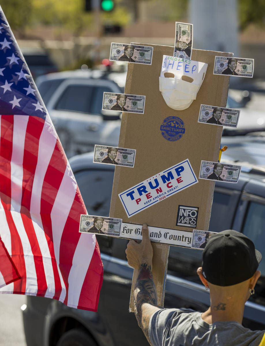 A variety of signs are displayed during the No Mask Nevada rally to oppose the face mask mandat ...