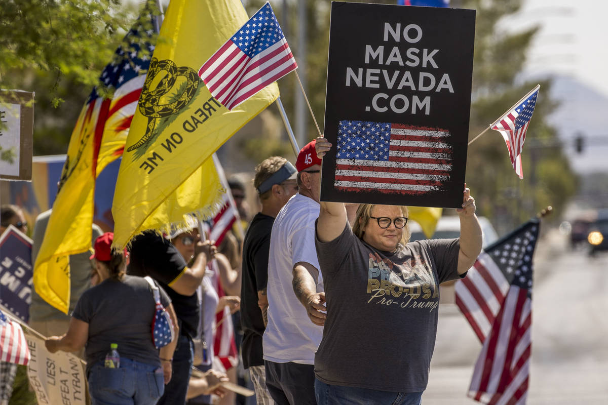Supporters hold signs and flags during the No Mask Nevada rally to oppose the face mask mandate ...