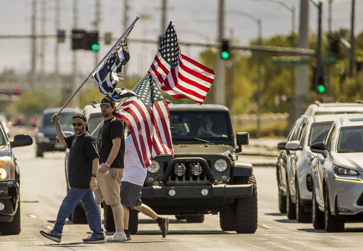 Supporters carrying flags make another cross of traffic during the No Mask Nevada rally to oppo ...