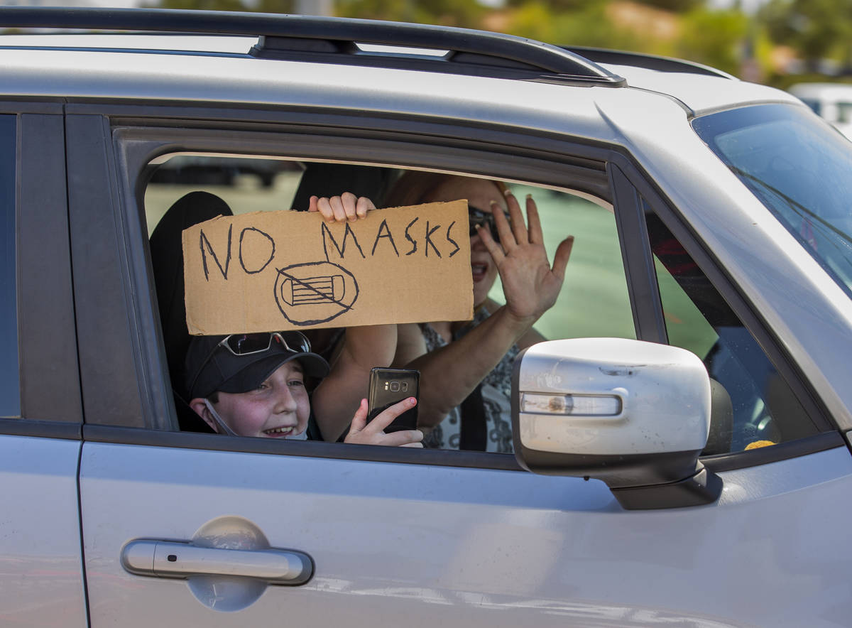 A passenger with sign and driver show their support as they pass by a No Mask Nevada rally to o ...
