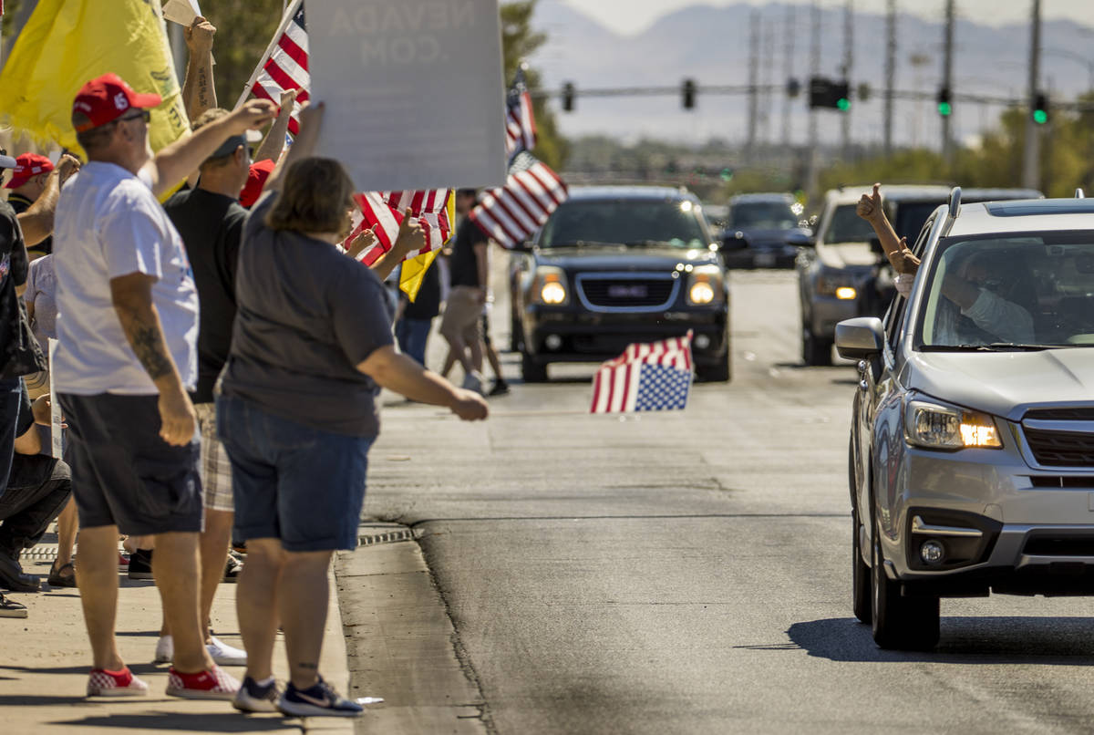 """A driver gives the """" thumbs up """" sign to supporters during a No Mask Nevada rally to ..."""