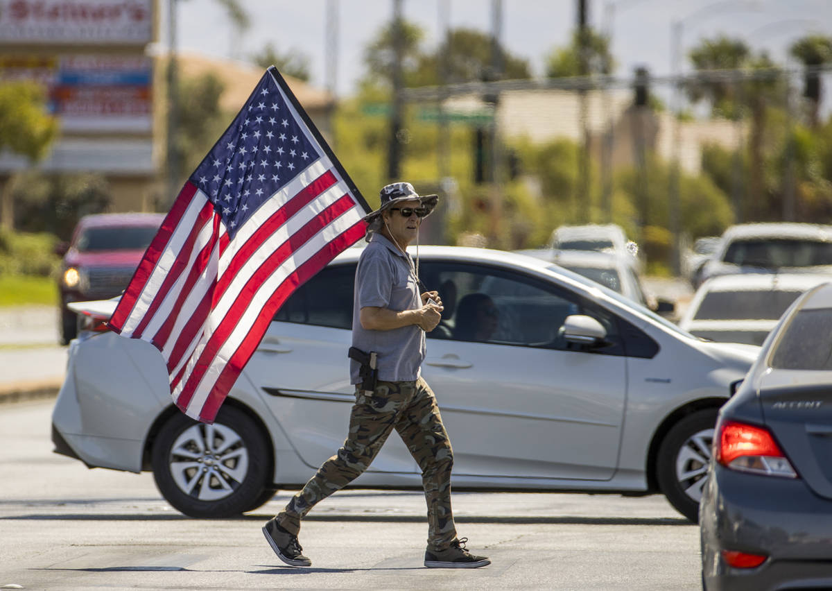 A supporter carrying a flag makes another cross of traffic during the No Mask Nevada rally to o ...