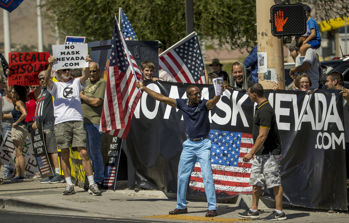 Mack Miller, center, is greeted by Anthony Mastrostefano, right, during a No Mask Nevada rally ...
