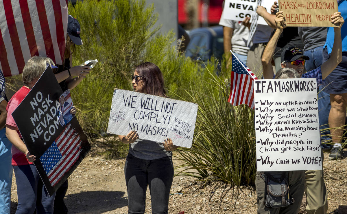 Supporters display a variety of signs during a No Mask Nevada rally to oppose the face mask man ...