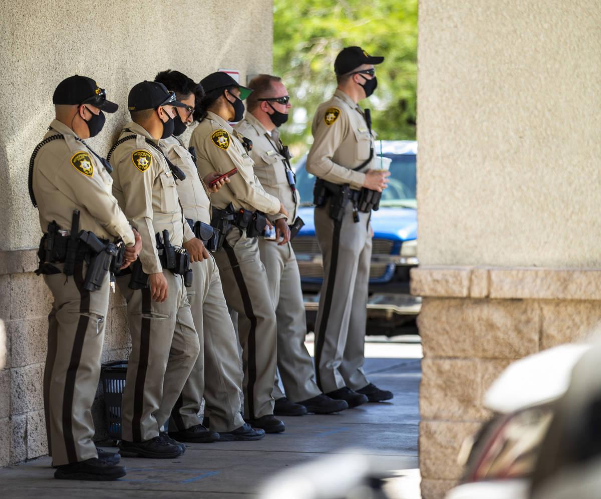 Las Vegas police officers keep cool at Walgreens while monitoring a No Mask Nevada rally to opp ...