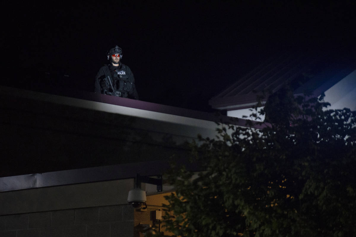 CORRECTS DAY TO FRIDAY - A Portland police officer watches from the roof of the Multnomah Count ...