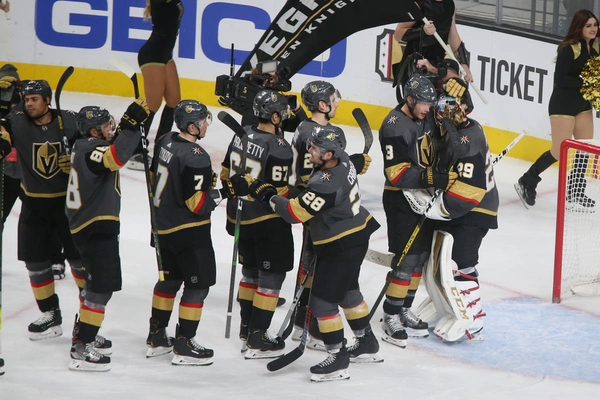 Vegas Golden Knights players lineup to embrace goaltender Marc-Andre Fleury (29) after the NHL ...