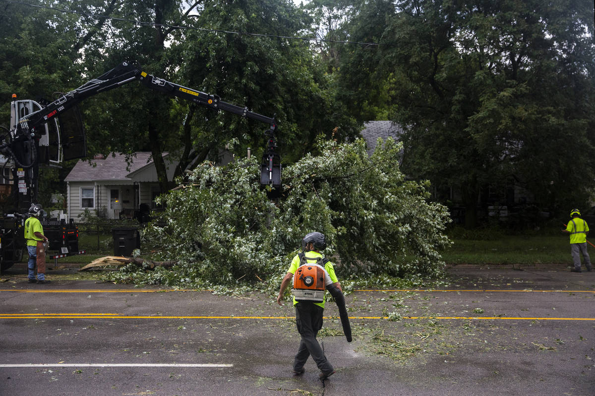 Des Moines city crews remove a tree fallen on Hickman Road, on Monday, Aug. 10, 2020, in Des Mo ...