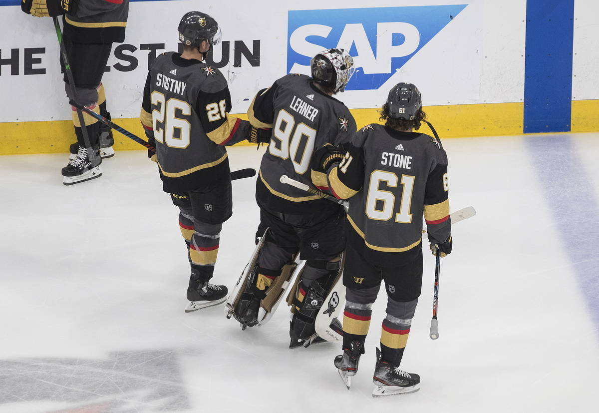 Vegas Golden Knights goalie Robin Lehner (90) is helped to the bench by Mark Stone (61) and Pau ...
