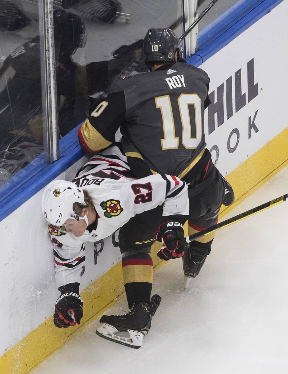 Chicago Blackhawks' Adam Boqvist (27) is hit by Vegas Golden Knights' Nicolas Roy (10) during t ...