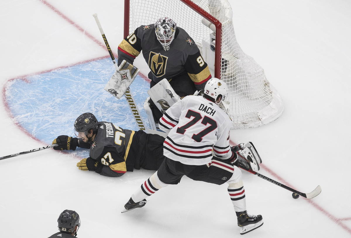 Chicago Blackhawks' Kirby Dach (77) is blocked by Vegas Golden Knights' Shea Theodore (27) as G ...