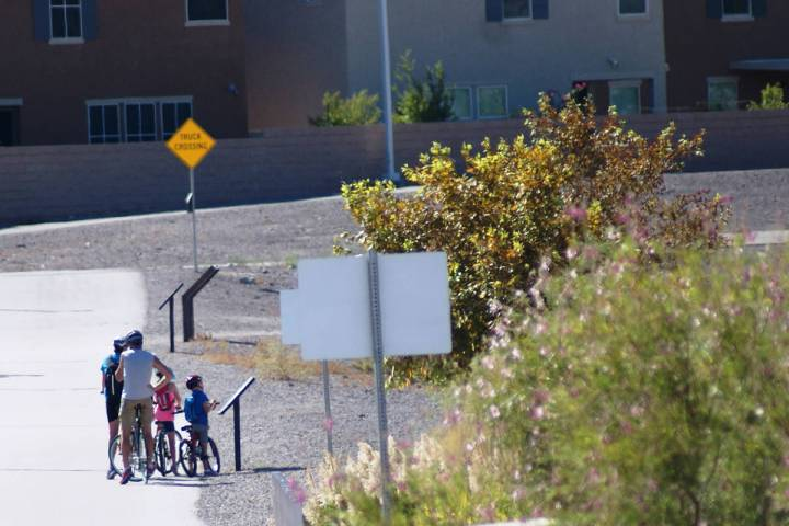 """A family biking at Cornerstone Park stops in late July to read a """"Story Walk"""" panel from the hu ..."""