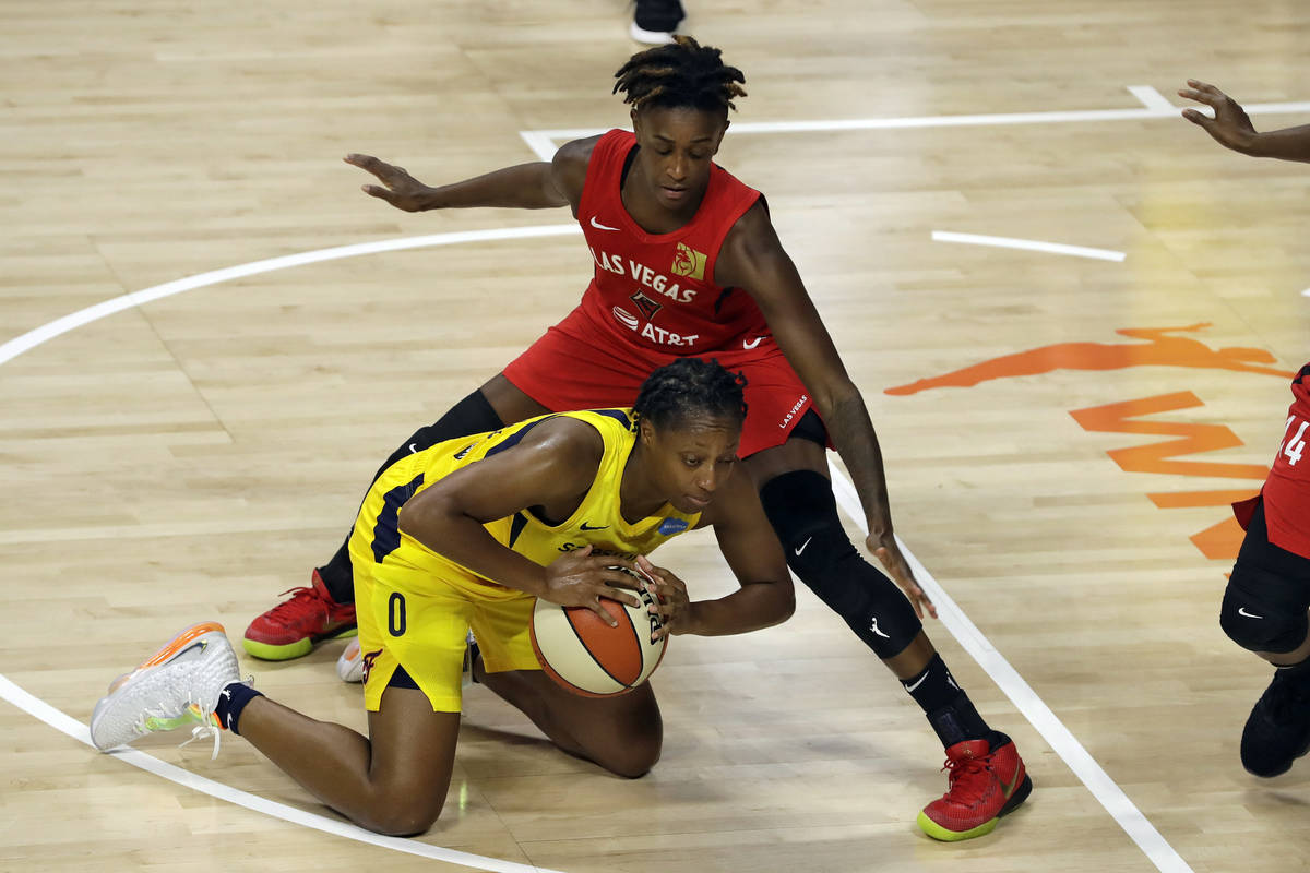 Indiana Fever guard Kelsey Mitchell (0) falls down in front of Las Vegas Aces forward Dearica H ...