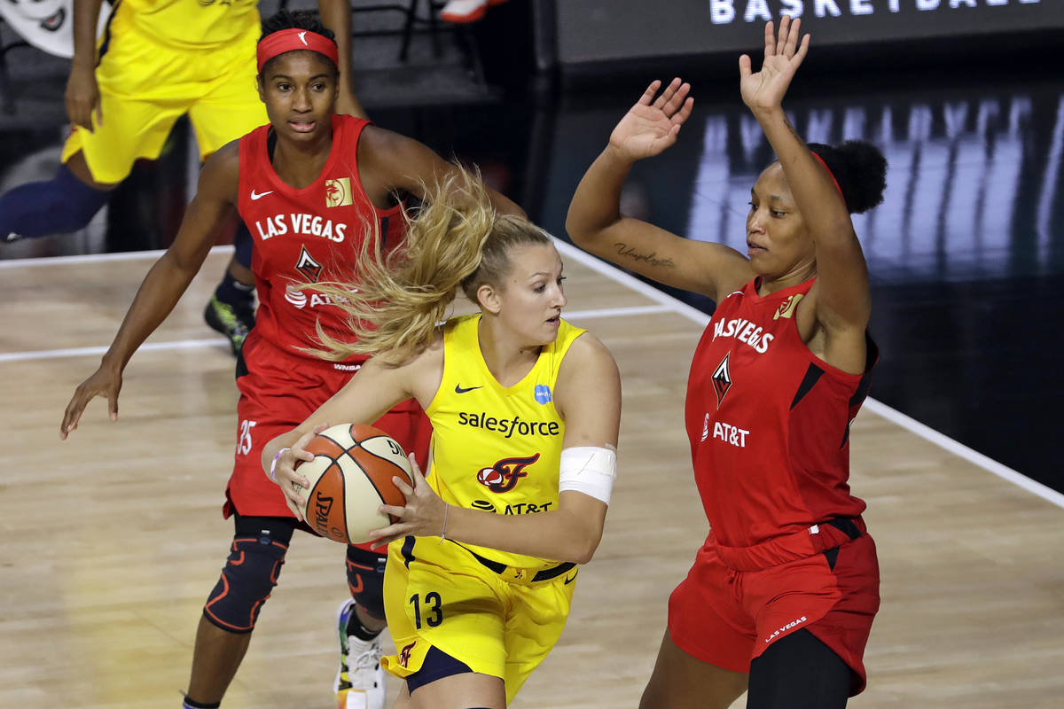 Indiana Fever forward Lauren Cox (13) drives into Las Vegas Aces center A'ja Wilson (22) and fo ...
