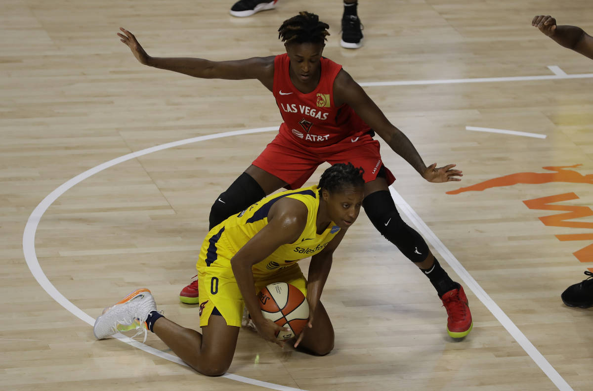 Indiana Fever guard Kelsey Mitchell (0) falls down in front of Las Vegas Aces guard Danielle Ro ...