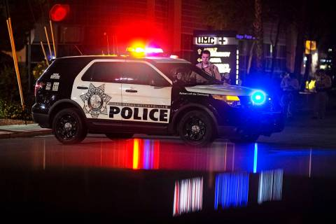 A group of Las Vegas Metro officers wait outside University Medical Center after an officer was ...