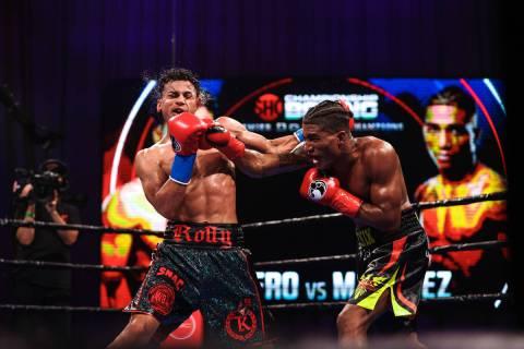 Rolando Romero takes a punch from Jackson Marinez during their WBA interim lightweight title fi ...