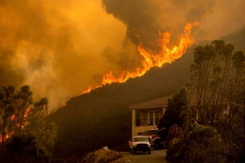 In a Monday, Aug. 17, 2020, file photo, flames from the River Fire crest a ridge in Salinas, Ca ...