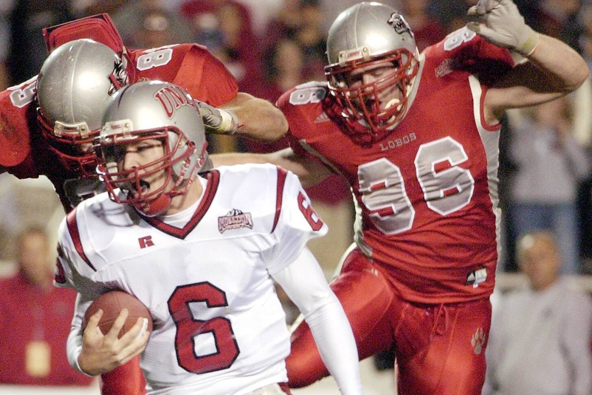 UNLV quarterback Scott Turner, center, runs from leaping New Mexico defenders Nick Speegle, lef ...