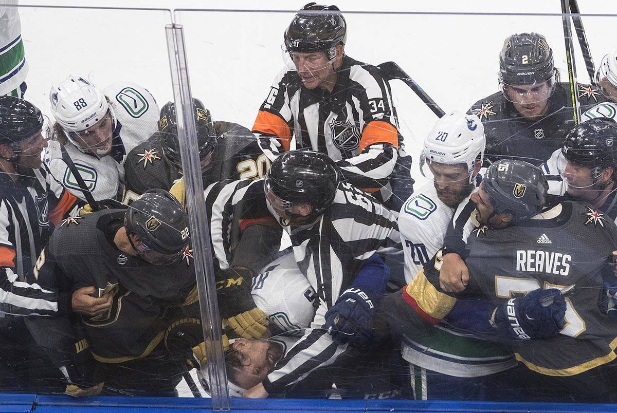 Vegas Golden Knights' Nick Holden (22) fights with Vancouver Canucks' Antoine Roussel, head at ...