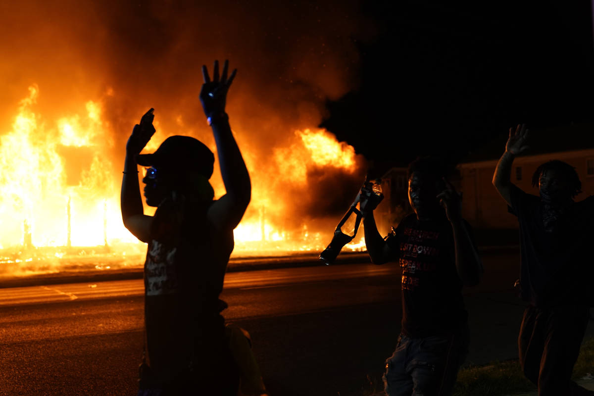 Protesters walk past police with their arms up, late Monday, Aug. 24, 2020, in Kenosha, Wis., a ...