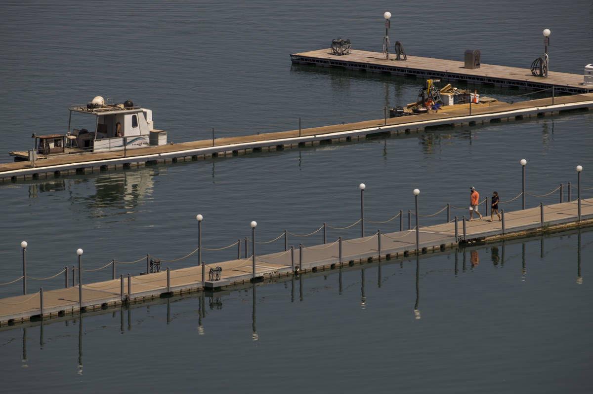 A couple walks along a dock at the Lake Mead Marina about the Lake Mead National Recreation Are ...
