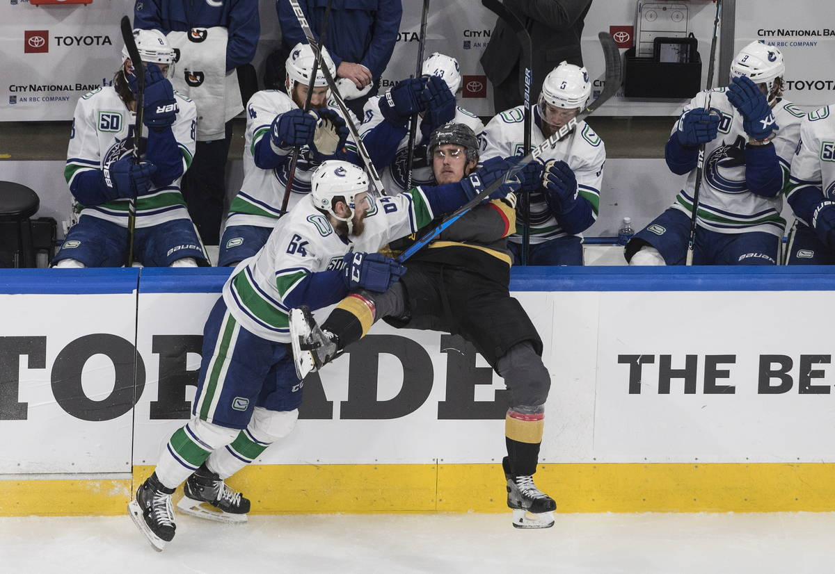 Vegas Golden Knights' Zach Whitecloud (2) is checked by Vancouver Canucks' Tyler Motte (64) dur ...