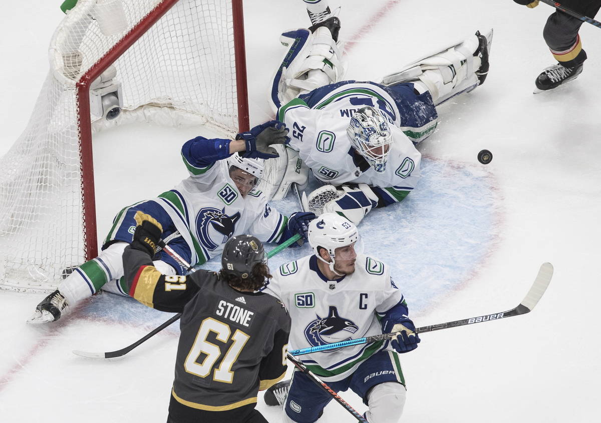 Vegas Golden Knights' Mark Stone (61) and Vancouver Canucks' Bo Horvat (53) battle in front as ...