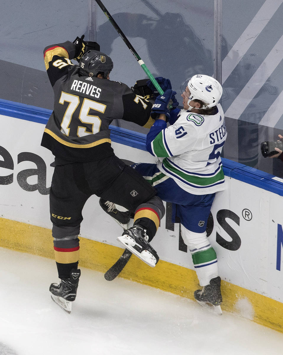Vegas Golden Knights' Ryan Reaves (75) checks Vancouver Canucks' Troy Stecher (51) during the f ...