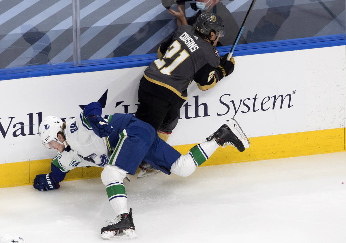Vegas Golden Knights' Nick Cousins (21) checks Vancouver Canucks' Adam Gaudette (88) during the ...