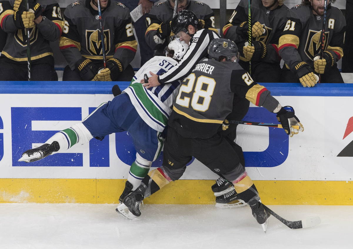 Vegas Golden Knights' William Carrier (28) and Vancouver Canucks' Troy Stecher (51) run into an ...