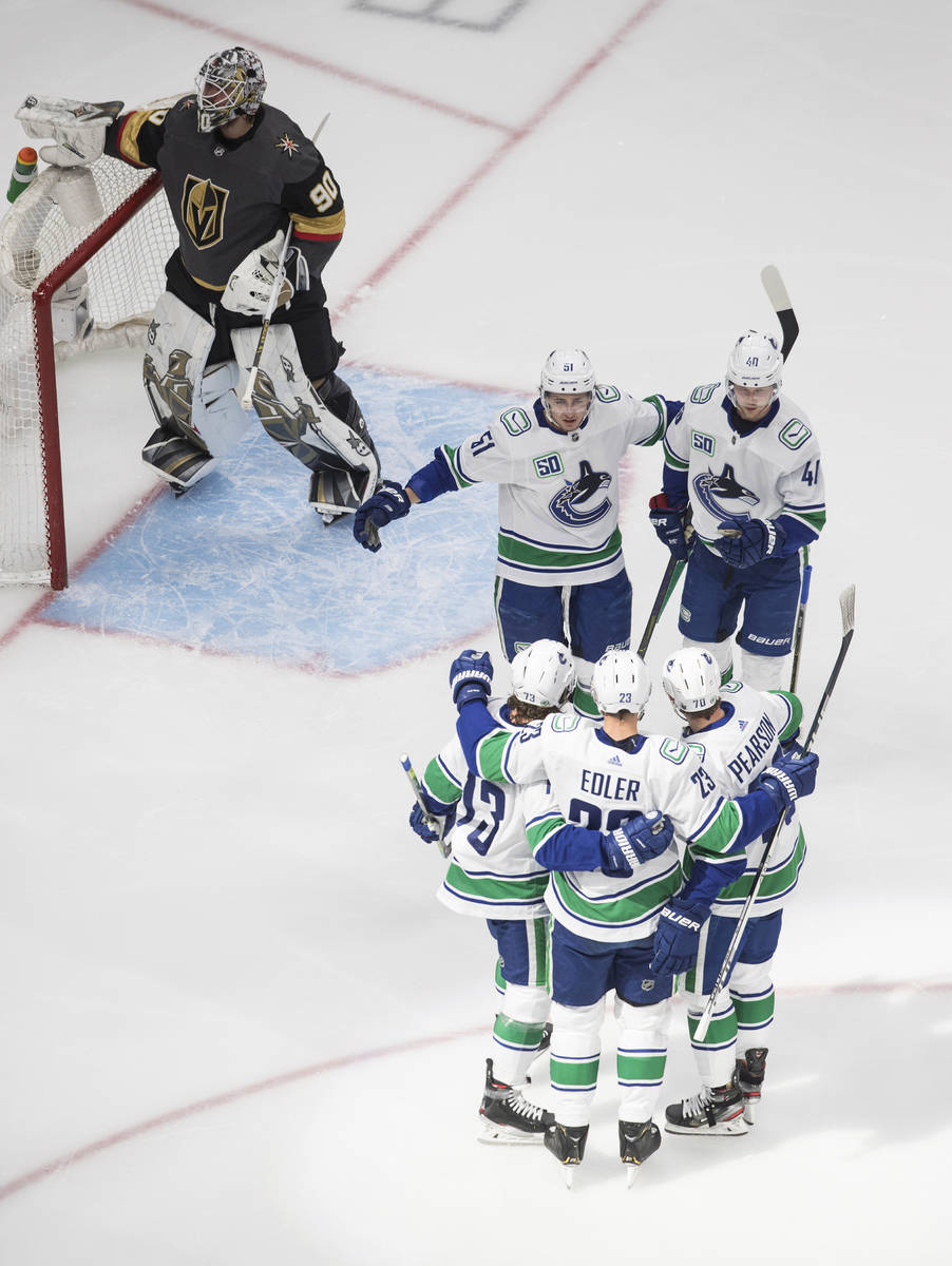 The Vancouver Canucks celebrate a goal on Vegas Golden Knights goalie Robin Lehner during the f ...