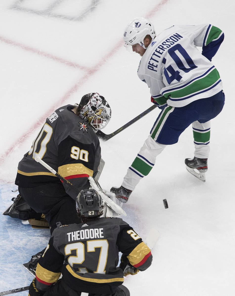 Vegas Golden Knights goalie Robin Lehner (90) stops Vancouver Canucks' Elias Pettersson (40) as ...