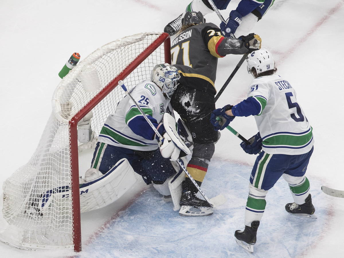 Vegas Golden Knights' William Karlsson (71) crashes against Vancouver Canucks goalie Jacob Mark ...